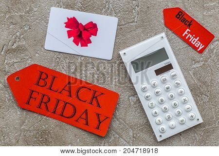 Words black friday on red label near card and calculator on light background top view.