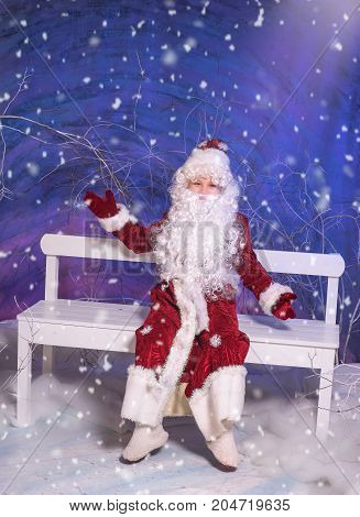 Vertical studio shot of a cheerful child wearing Santa Claus costume and sitting on bench