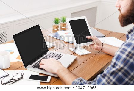 Young casual male employee typing on laptop with tablet in modern office, crop, close up