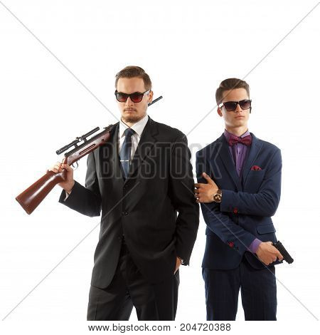 Two young men in formal wear with guns.