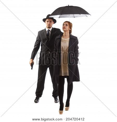 A lady in formal wear with her bodyguard holding an umbrella