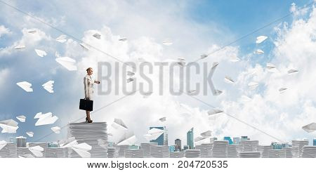 Confident business woman in suit standing among flying paper planes with cloudly skyscape on background. Mixed media.