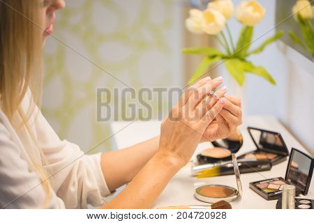 Portrait of young beautiful blonde hair woman sitting near dressing table and doing makeup at home.
