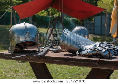 Close Up Of Medieval Silver Helmet On Wooden Table With Knight's Garment