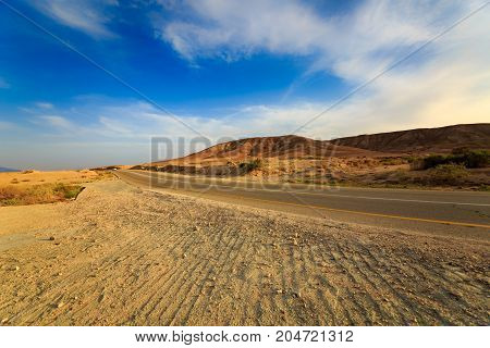 Road with car in a mountains in desert Negev at sunset