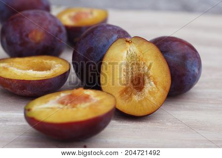 Plums on a white ristic wooden background