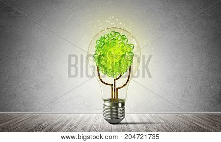 Glass lightbulb with tree from gears inside placed in empty room with grey wall on background. 3D rendering.