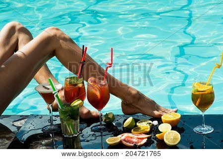 Cocktail and sexy leg of girl in pool. Woman with alcoholic beverage and fruit. Drink and food. Swimming and relax in water pool. Summer vacation and party.
