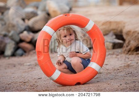 Emergency and safety on water on summer vacations. Boy child playing with life saver. Baby care and childhood concept. Happiness and expressive emotions. Kid looking through orange life ring at beach.