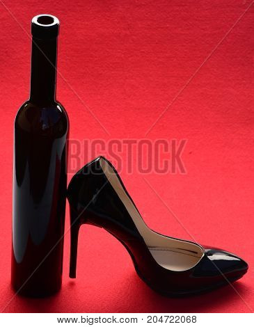 bottle of wine and shoe black color on high heel on red background fashion and beauty shopping valentines day and date
