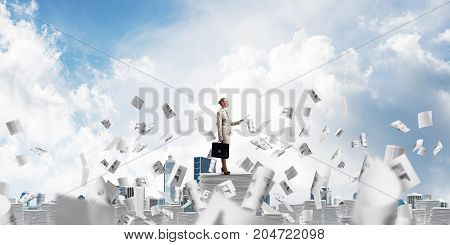 Confident business woman in suit standing among flying papers with cloudly skyscape on background. Mixed media.