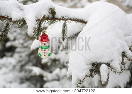 Snowman Toy Hanging On Fir Tree In Winter Wood Background