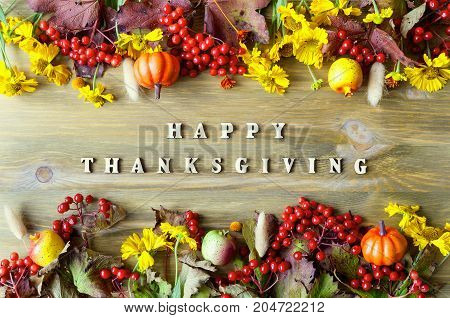 Thanksgiving day autumn background. Happy Thanksgiving letters seasonal autumn nature berries pumpkins apples and flowers on the wooden background. Happy Thanksgiving background