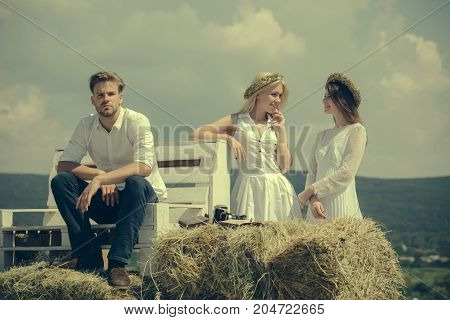 Man or macho sitting on bench. Happy girls and women smiling on mountain landscape. Friends enjoying sunny summer day on nature. Vacation wanderlust and traveling. Friendship and people concept.