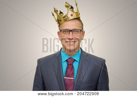 Winner. Award ceremony. First place man. Top manager. Young successful business man in suit and glasses with golden crown on his head. Vip client. Premium user. Success.