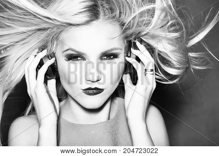 young woman or girl dj with blonde hair and red lips on pretty serious sexy face in yellow shirt with musical stereo headphones or headset in studio on pink background