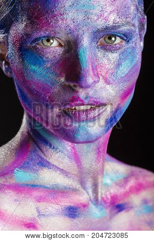 Fantasy makeup. Woman with colorful makeup and body art against black background. Fashion