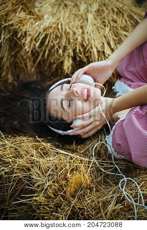 Summer vacation concept. Woman with headphones relaxing in hay. Leisure and entertainment. Girl listening music with closed eyes. Lifestyle and technology.