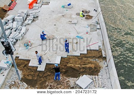 Moscow Russia - August 31 2016: Workers laying paving road tiles on the waterfront in Moscow