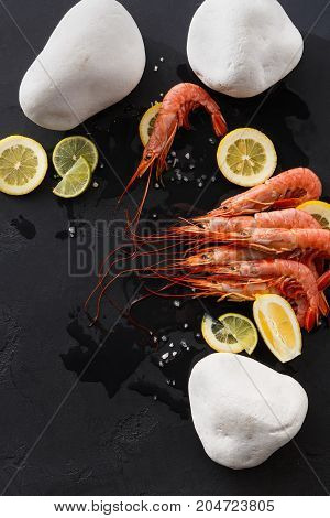 Shrimps with lemon and white stones on black background, copy space. Top view on appetizing seafood snack, restaurant serving.
