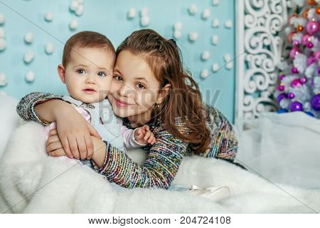 Two sisters hug. Children. The concept of Merry Christmas New Year family.