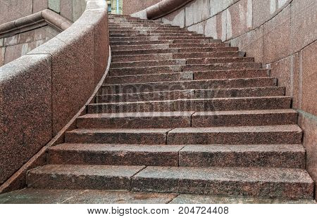 Steps of pink granite on the embankment of the Neva river in Saint-Petersburg.