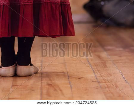 A dancer standing in a dance school room attending a lesson