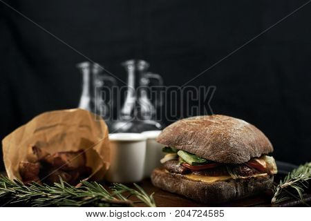 Craft beef burger on wooden table on dark blue background.