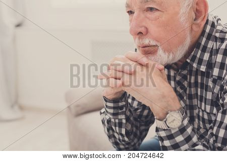 Pensive elderly man sitting on couch with thoughtful facial expression, copy space