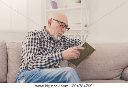Senior man reading book sitting on sofa at home, copy space