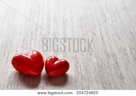 Two candy hearts for Valentine's Day with grey background.