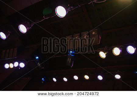 Color light in the concert stage. Color flood light on the ceiling. Soffits light illuminate the scene. Electric light. Light equipment on stage for a concert. Ray of light