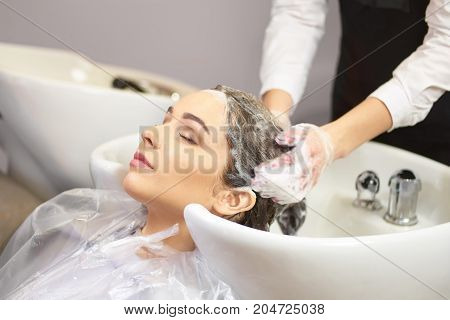 Lady getting her head washed. Young female in beauty salon. Professional hair care products.