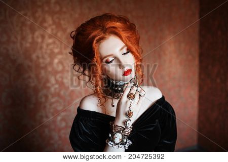 A gothic woman is a vampire with pale skin and red hair in a black gothic dress and a gothic necklace on her neck. Gothic girl witch with vampire claws and red lips. Gothic look. Gothic outfit for halloween.