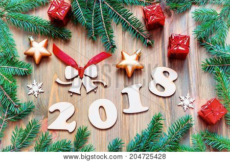 Happy New Year 2018 background with 2018 figures Christmas toys green fir tree branches. New Year 2018 still life