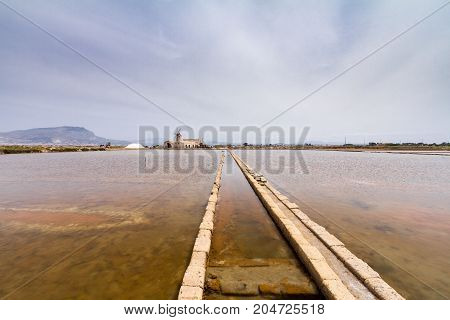 Historical salt flats in Trapani. The salt culture extraction and production in this city represents one of the major economic revenue and it is one of the oldest traditions