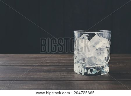 Glass with ice cubes on dark background. Cold summer cocktail preparing, refreshment concept