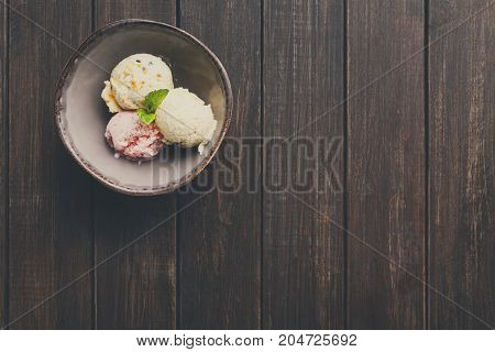 Assorted ice cream scoops in bowl top view. Delicious cold sweet dessert on wooden table, copy space