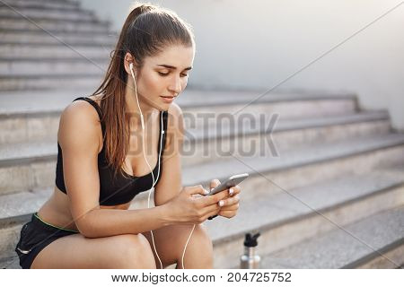 Female fitness trainer using a smart phone selecting music for her early morning workout in a busy city. Urban sport concept.