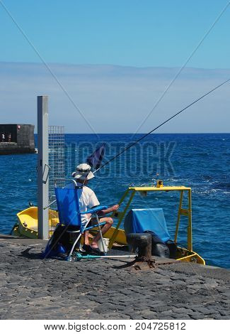 man fishing on a harbour with rod sitting in a chair next to a boat