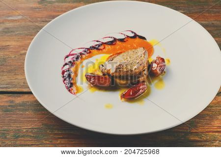 Roasted goose liver with date and apple, fruit and berry sauce painting. Creative french cuisine, delicatessen restaurant meal