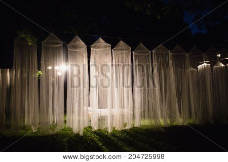 The white long canopies are illuminated by the light of the lantern on a dark night. Conceptual photography with canopy. A white canopy. Canopy on a dark background. Conceptual picture with canopy. Many canopies
