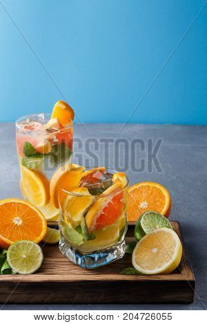 Summer citrus drinks at blue background. Healthy detox water in glasses and fruits variety on wooden board. Colorful backdrop with oranges, lemon and lime, copy space