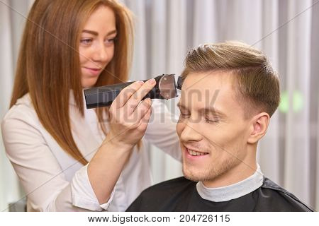 Barber using hair clipper. Man in hair salon smiling.