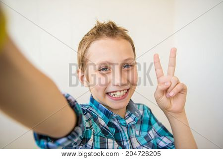 Happy boy making selfie and showing thumb up