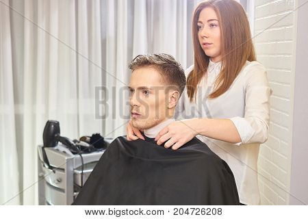 Young caucasian man, hair salon. Female barber and her customer.