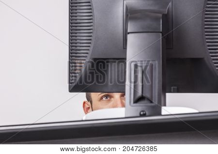 Interesting image of the eye of a young man looking to the monitor at his workplace.
