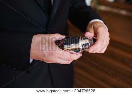 A stylish man in a dark jacket with a bottle of perfume. A businessman in a respectable suit is holding a bottle of perfume in his hands. Man perfume. Perfume smell