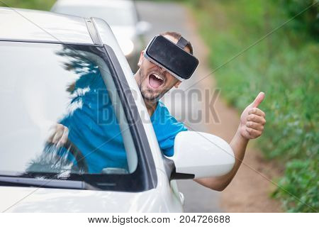 Portrait of young man leaning on car window using virtual reality glasses and showing thumbs up. Road in the background