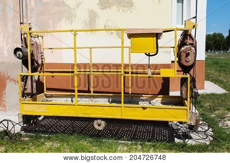 Construction cradle on the background of the wall of the house. Yellow work cradle. Work cradle in the background of the house. Work cradle hanging on wall background